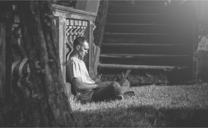 Mann mit Laptop auf Rasen, gegen Mauer