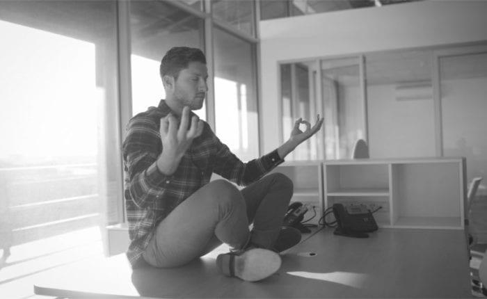 mann meditiert auf tisch, büro, führung